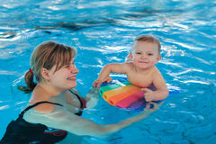 Little baby with blue eyes learning to swim Royalty Free Stock Photos