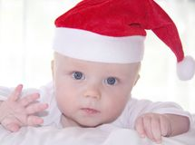 Little baby with blue eyes in red new year hat Royalty Free Stock Photo