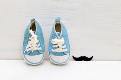 Little baby blue sneakers for boy and mustaches on a white woode Royalty Free Stock Images