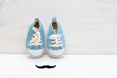 Little baby blue sneakers and mustaches on a white wooden backgr Stock Image