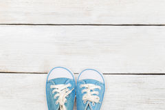 Little baby blue sneakers on a white wooden background Stock Image