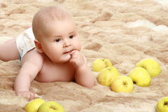 Little baby boy in apples. Thoughtful little baby boy in apples royalty free stock photo