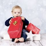 Little baby boy with big christmas presents. Studio portrait of surprised toddler on Christmas Royalty Free Stock Images