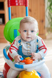 Little baby boy in blue big toy car indoor Royalty Free Stock Image