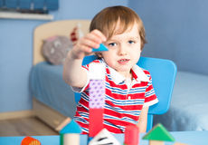 Little baby boy is building with wooden toy blocks Royalty Free Stock Photos