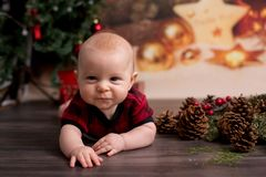 Little baby boy with christmas clothes, lying on the floor. With christmas decoration around him stock image