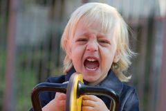 Crying little child on playground Stock Photos