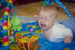 Little baby boy crying. Little six months old baby boy crying bitterly, lying on his stomach on the play mat and looking on the toys. Kid getting frustrated with royalty free stock photo