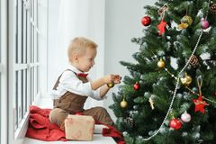 Little baby boy decorating a Christmas tree toys. Holidays, gift, and new year concept Stock Photography