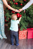 Little baby boy decorating a Christmas tree toys. Holidays, gift, and new year concept Royalty Free Stock Photos