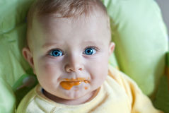 Little baby boy with dirty face eating fruit mash Stock Images