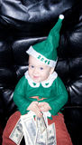 Little baby boy with dollars. Little baby boy in green santa suit and hat sits with dollars in hands Stock Photos