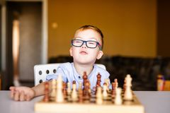 Little baby boy with down syndrome with big blue glasses playing chess in kindergarten stock photography