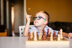 Little baby boy with down syndrome with big blue glasses playing chess in kindergarten stock photo
