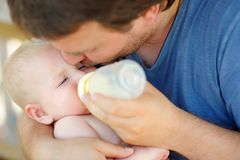 Little baby boy drinking milk from bottle. Adorable baby boy drinking milk from bottle in father hands Stock Image
