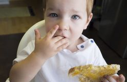 Little baby boy eating peach jam toast royalty free stock photos