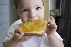 Little baby boy eating peach jam toast royalty free stock image