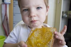 Little baby boy eating peach jam toast royalty free stock photo