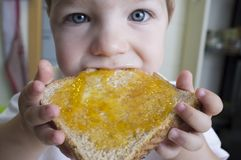 Little baby boy eating peach jam toast stock images