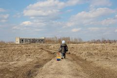 Little baby boy goes on the road across the field to the unfinished building wheels car toy royalty free stock photography