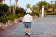 Little baby boy in a hat and shorts goes ahead in summer, view f. Rom the back Royalty Free Stock Images