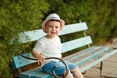 Little baby boy in a hat sitting on a bench and smiling in the s Stock Image