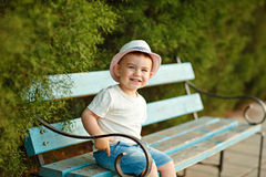 Little baby boy in a hat sitting on a bench and smiling in the s Stock Photos