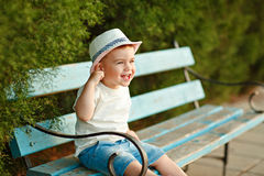 Little baby boy in a hat sitting on a bench in the summer and ch Royalty Free Stock Photography