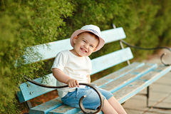 Little baby boy in a hat sitting on a bench in the summer and ch Stock Image