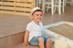 Little baby boy in the hat sitting on the steps of the house in Royalty Free Stock Image