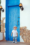 Little baby boy in a hat standing by the house about a blue door stock photo