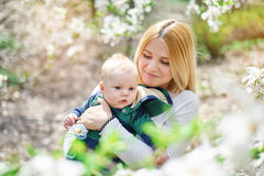 Little baby boy with her young mother in the blossoming Spring garden Stock Images