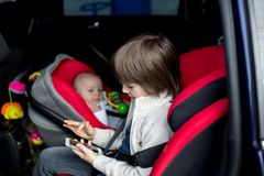 Little baby boy and his older brother, traveling in car seats, g. Oing on a holiday, preschool boy playing with mobile phone Royalty Free Stock Photos
