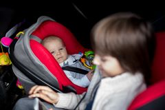 Little baby boy and his older brother, traveling in car seats, g. Oing on a holiday, preschool boy playing with mobile phone Royalty Free Stock Image