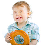 Little baby boy holding a bagel Royalty Free Stock Photos