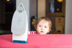 Little Baby Boy Is Reaching To Hot Iron Stock Image