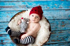 Little baby boy with knitted hat in a basket, happily smiling Stock Image