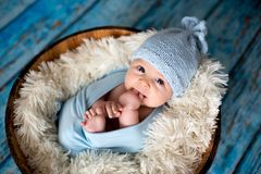 Little baby boy with knitted hat in a basket, happily smiling Stock Photo