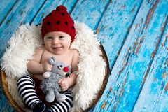 Little baby boy with knitted hat in a basket, happily smiling Royalty Free Stock Photos