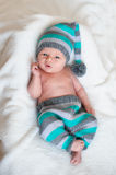 Little baby boy in a knitted hat lying on the white bed Royalty Free Stock Photo