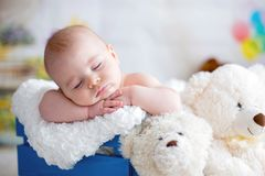 Little baby boy with knitted hat, sleeping with cute teddy bear Royalty Free Stock Photos