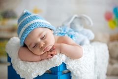 Little baby boy with knitted hat, sleeping with cute teddy bear. Toy at home stock image