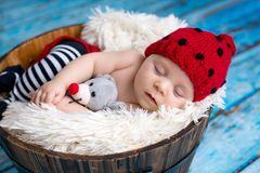 Little baby boy with knitted hat in a basket, happily smiling Stock Photos