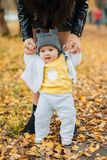 Little baby boy learns to take first steps holding mom`s hands in autumn stock photography