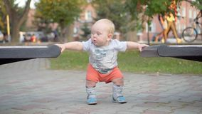 Little baby boy learns to walk along the bench. In the park. Outdoor. Stock Image