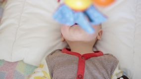 Little baby in the crib. Little baby boy lies in a crib and looks at the toys that hang on top stock video footage