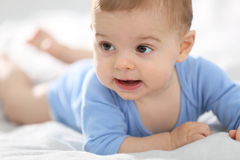 Little baby boy lying on bed crawling Stock Images