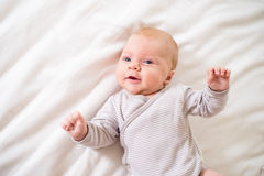 Little baby boy lying on bed in onesie, white bedroom Royalty Free Stock Image
