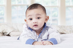 Little baby boy lying in the bedroom Royalty Free Stock Image
