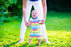 Little baby boy making first steps. Baby boy making his first steps. Mother holding her child. Kid walking on a lawn in a sunny summer garden. Kids learning to Royalty Free Stock Photo